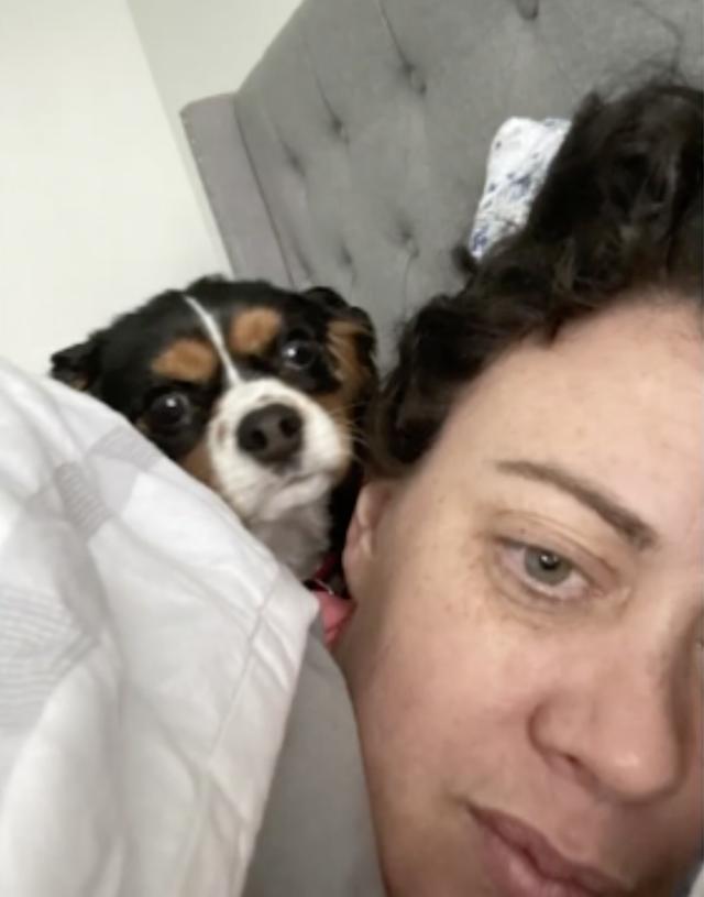 Woman cuddling King Charles Spaniel